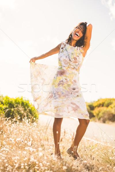 Beautiful woman in floral dress smiling at camera Stock photo © wavebreak_media