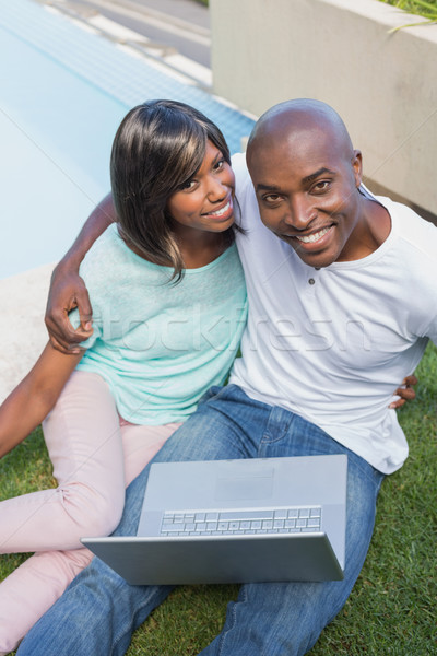 Happy couple sitting in garden using laptop together Stock photo © wavebreak_media