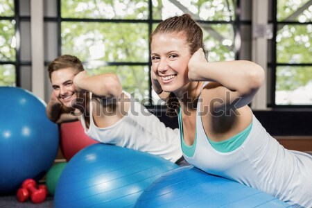 Couple doing sit ups on exercise balls Stock photo © wavebreak_media