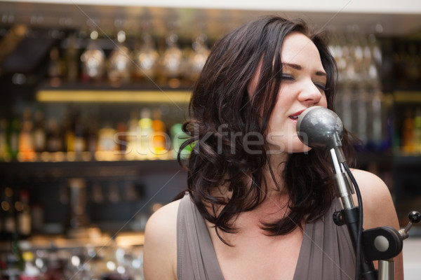 Brunette haired woman singing in a microphone Stock photo © wavebreak_media