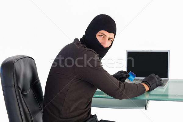 Burglar shopping online with laptop while looking at camera Stock photo © wavebreak_media