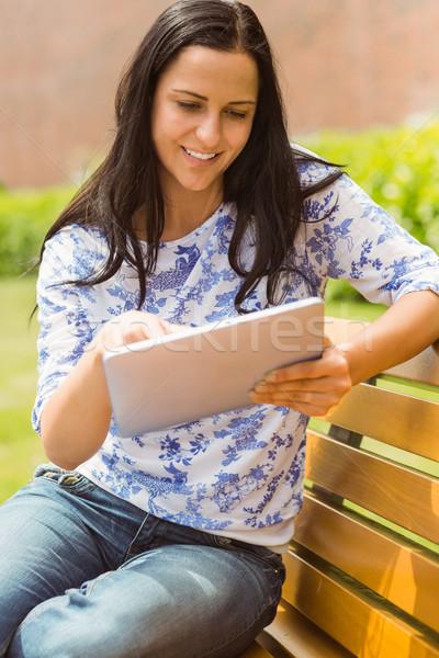 Happy brunette sitting on bench using tablet pc Stock photo © wavebreak_media