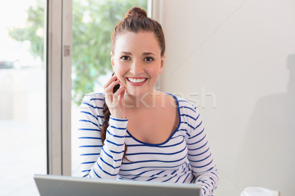 Stock photo: Pretty brunette catching up on work