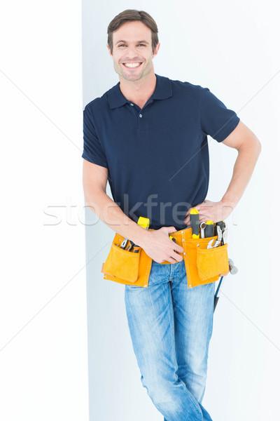 Man with tool belt around waist against white background Stock photo © wavebreak_media