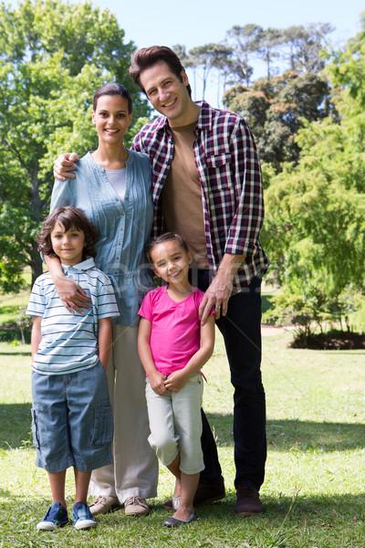 Boldog család mosolyog kamera napos idő fa fű Stock fotó © wavebreak_media