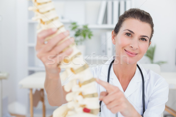 Happy doctor showing anatomical spine Stock photo © wavebreak_media