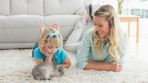 Smiling daughter and mother laying on the floor with rabbit Stock photo © wavebreak_media