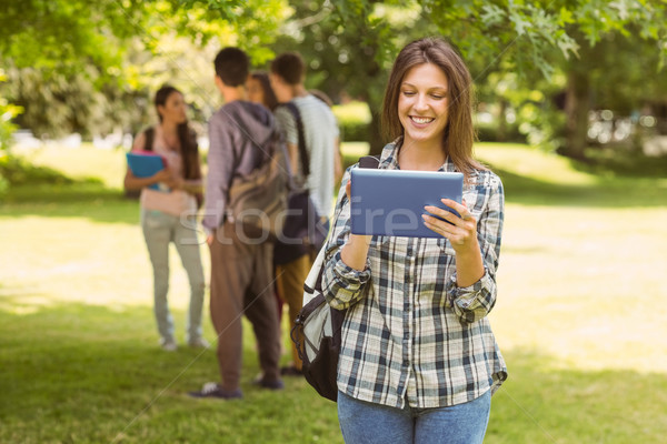 Smiling student with a shoulder bag and using tablet computer Stock photo © wavebreak_media