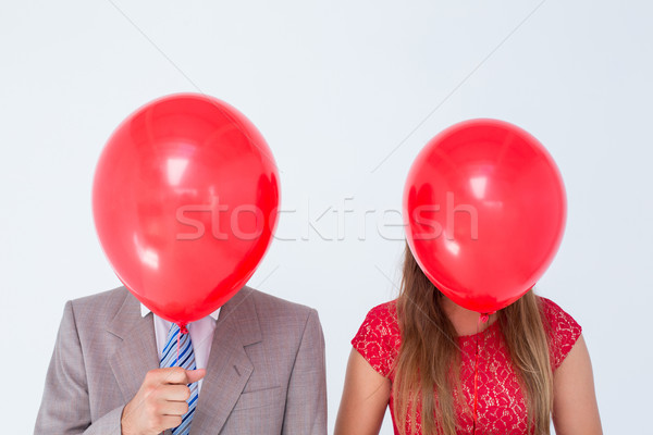 Geeky couple holding balloons in front of their faces  Stock photo © wavebreak_media