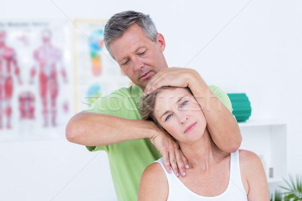 Doctor doing neck adjustment Stock photo © wavebreak_media