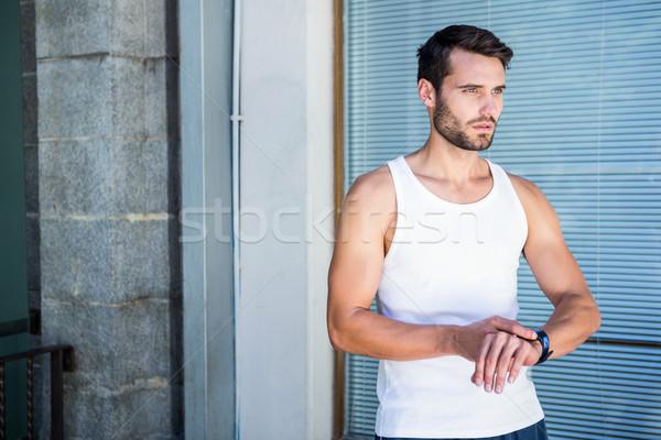 Handsome athlete checking heart rate watch Stock photo © wavebreak_media