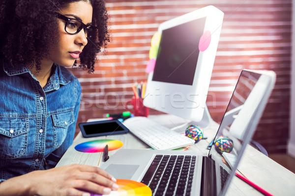Casual female designer using laptop Stock photo © wavebreak_media