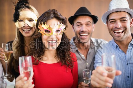 Composite image of portrait of friends holding champagne glasses while laughing Stock photo © wavebreak_media