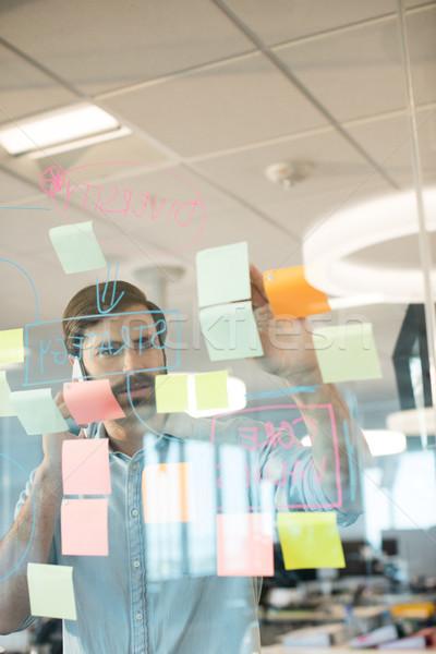 Businessman analyzing adhesive notes while using mobile phone Stock photo © wavebreak_media