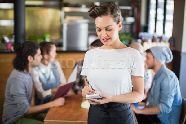 Belle serveuse permanent clientèle restaurant écrit Photo stock © wavebreak_media