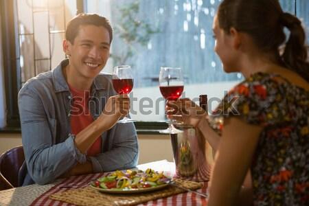 Stock photo: Couple toasting glasses of wine while having meal