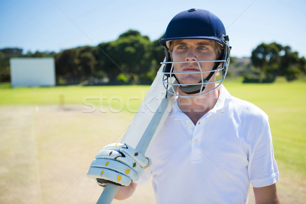 Thoughtful cricket player holding bat while wearing helmet Stock photo © wavebreak_media