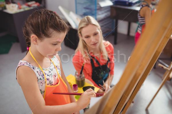 Teacher assisting girl in drawing class Stock photo © wavebreak_media