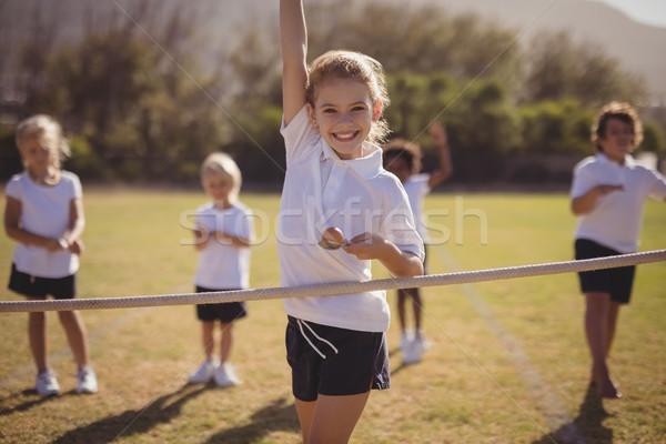 Portrait of happy schoolgirl wining egg and spoon race Stock photo © wavebreak_media