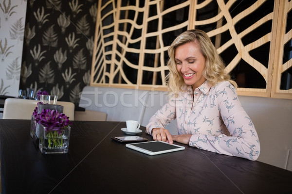 Businesswoman using digital tablet and mobile phone while sitting in restaurant Stock photo © wavebreak_media