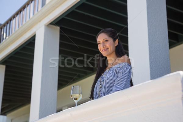 Mosolyog fiatal nő áll borospohár erkély alulról fotózva Stock fotó © wavebreak_media