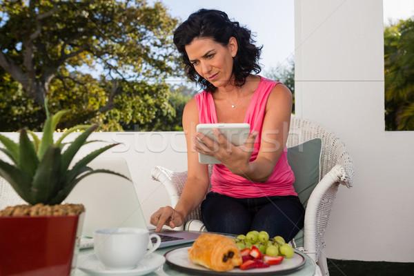 женщину цифровой таблетка используя ноутбук таблице Сток-фото © wavebreak_media
