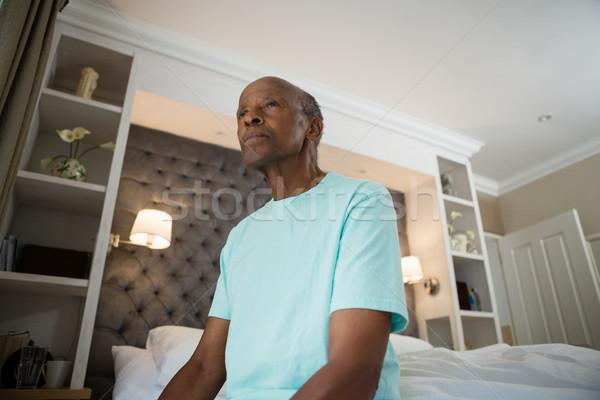 Thoughtful senior man looking away while sitting at home Stock photo © wavebreak_media