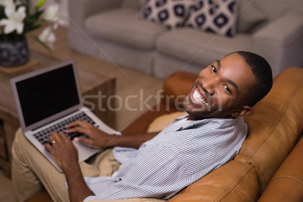 Portrait of happy young man using laptop at home Stock photo © wavebreak_media