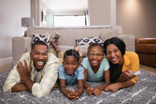 Smiling family watching television while lying on rug at home Stock photo © wavebreak_media