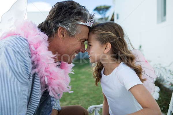 Smiling father and daughter in fairy costume standing face to face Stock photo © wavebreak_media