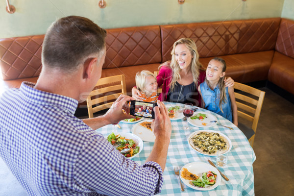 High angle view of father photographing family at restaurant Stock photo © wavebreak_media