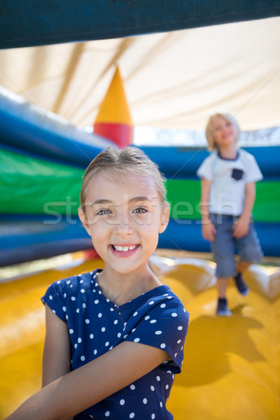 Girl sitting on bouncy castle while brother playing in background Stock photo © wavebreak_media