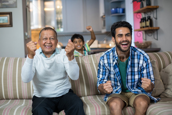 Family clenching fist while watching soccer match Stock photo © wavebreak_media