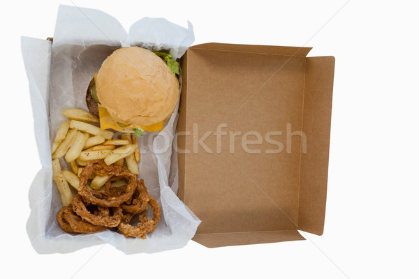 Hamburger, onion ring and french fries in a take away container on table Stock photo © wavebreak_media