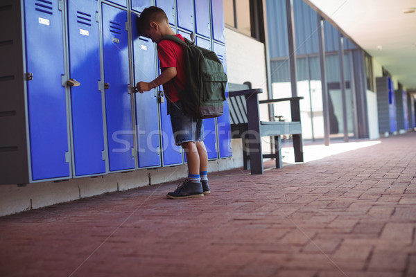 Stock photo: Full length of boy leaning on lockers in corridor