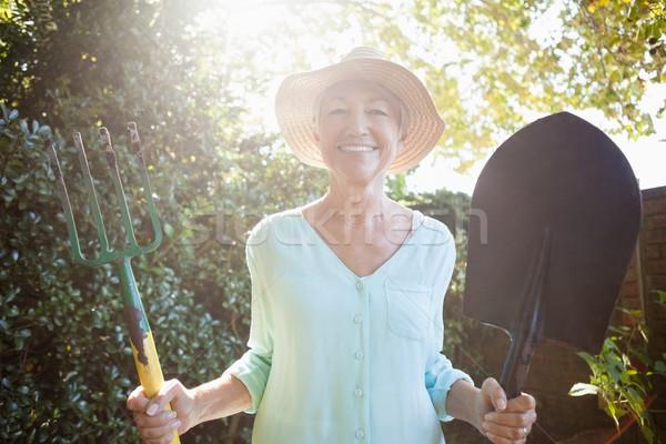 Back lit portrait of smiling senior woman holding garden fork and shovel Stock photo © wavebreak_media