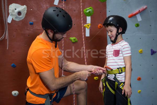 Trainer assisting boy to wear safety harness Stock photo © wavebreak_media