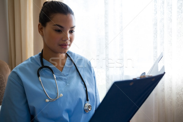 Female doctor reading reports while standing in nursing home Stock photo © wavebreak_media
