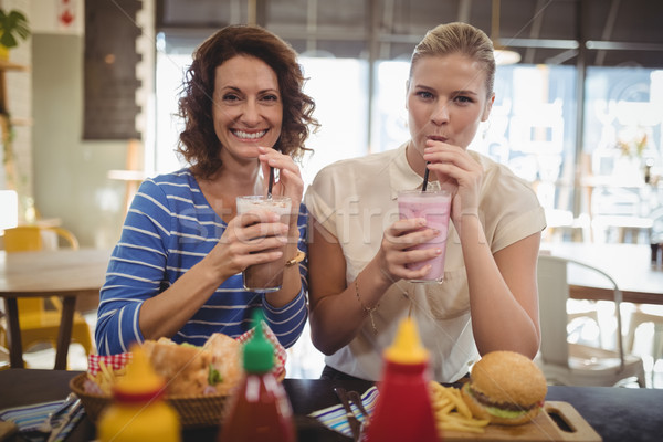 Portrait of smiling female friends drinking milkshake while sitting at cafe Stock photo © wavebreak_media