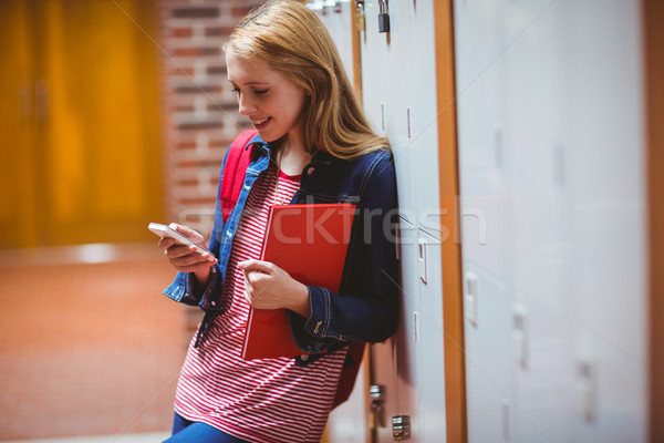 Smiling student leaning against the locker using smartphone Stock photo © wavebreak_media