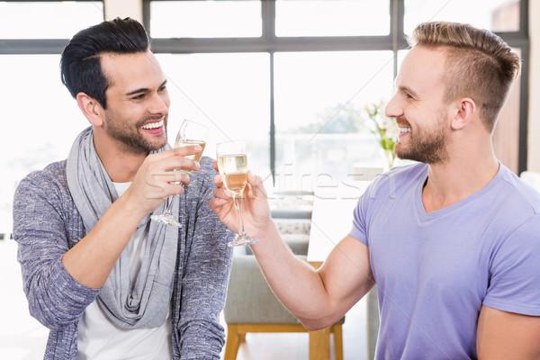 Sorridente homossexual casal champanhe casa Foto stock © wavebreak_media