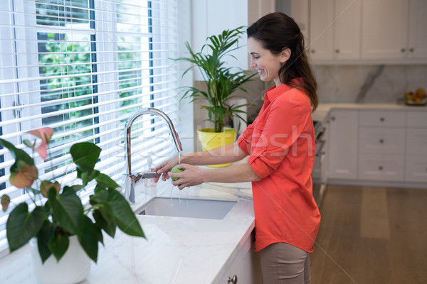 Woman washing fruit in kitchen Stock photo © wavebreak_media