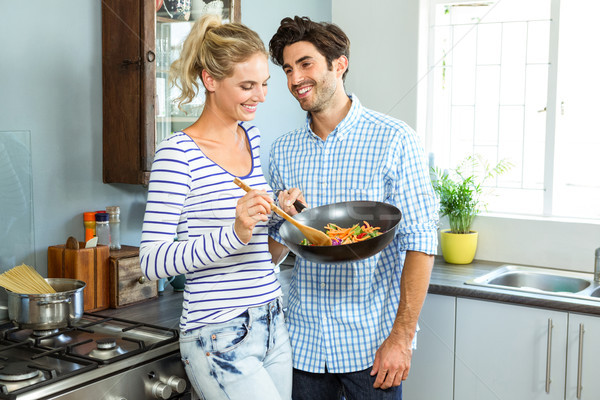 Young couple preparing food together in kitchen Stock photo © wavebreak_media