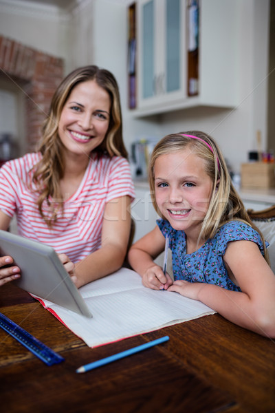 Mother using a digital tablet while helping daughter with her ho Stock photo © wavebreak_media