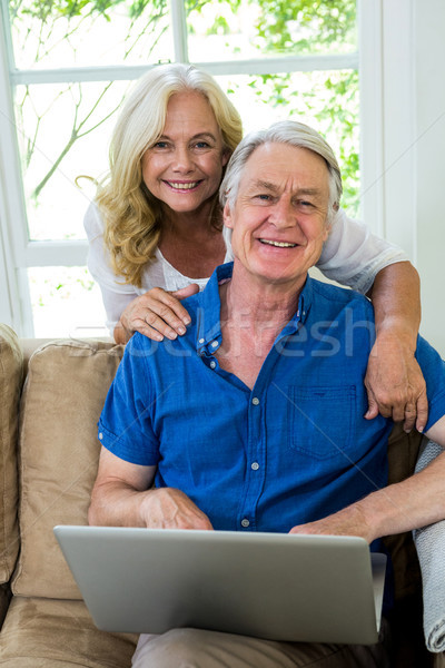 Happy senior couple with laptop sitting on sofa at home Stock photo © wavebreak_media