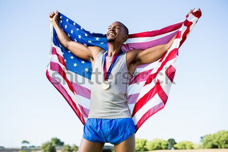 Atleta posando bandeira americana estádio homem vento Foto stock © wavebreak_media