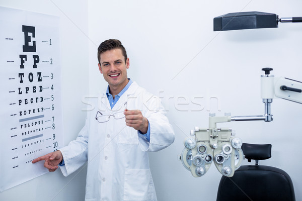 Optometrist pointing at eye chart Stock photo © wavebreak_media