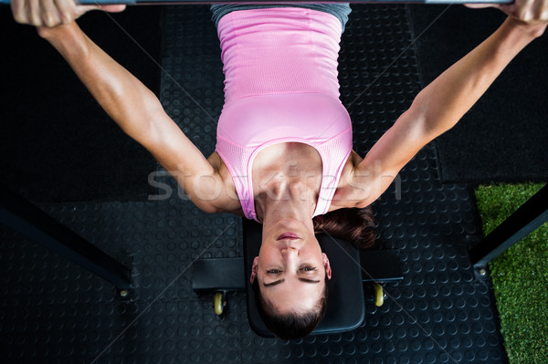 Woman holding barbell while lying on bench press in gym Stock photo © wavebreak_media