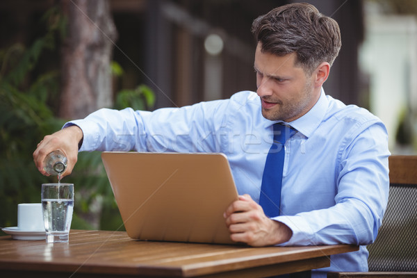 Handsome businessman pouring drink in glass while using laptop Stock photo © wavebreak_media