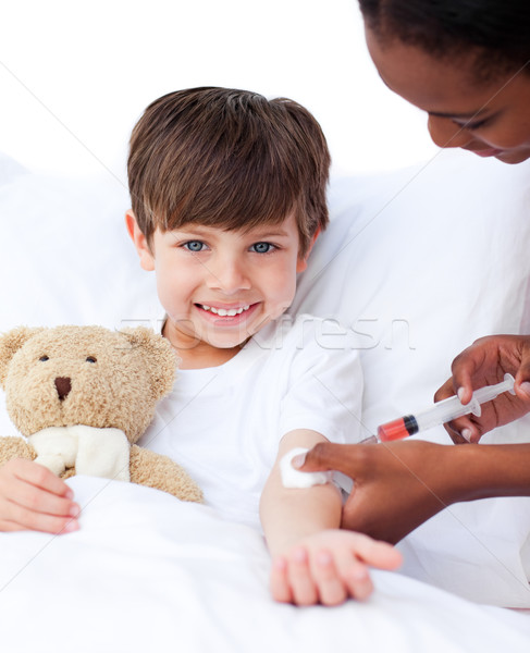 Stock photo: Smiling little boy receiving an injection